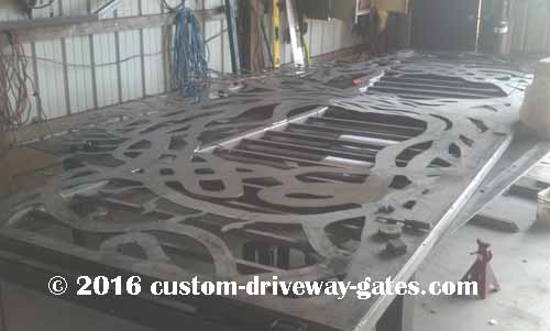 picket-style-driveway-gate-with-artistic-tree-design