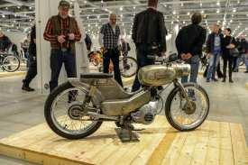 Der Spatz war das kleinste Kraftrad aus der sogenannten Vogelserie des früheren Thüringer Zweiradherstellers VEB Simson aus Suhl. Es gab ihn in drei verschiedenen Versionen: Eine als Moped mit Pedalen sowie zwei als Mokick mit Kickstarter – eines davon mit Rheinmetall-Motor aus Sömmerda, eines mit Simson-Aggregat. Der Spatz wurde von 1964 bis 1970 produziert, immerhin 152000 Stück Exemplare liefen von den Bändern. Dieses kecke Vögelchen hier wird von einem Gebläsemotor aus einer Simson Schwalbe angetrieben, der gut dreieinhalb Pferdestärken freisetzt. Das hintere Schutzblech wurde am Rahmen verschweißt, die Felgen von 1,5 auf 2,5 Zoll verbreitert und mit BMX-Reifen besohlt. Verschweißt wurden auch der Tank mit der Lampenmaske sowie die Tankanzeige. Das Simson-Emblem ist eingeätzt. In Kombination mit dem blank geschliffenen Metall und dem fehlenden vorderen Schutzblech ergibt sich so ein wirklich cooler Spatzen-Look, mit dem man auch heute noch vor jeder Schule punkten könnte.