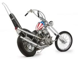 CAPTAIN AMERICA – Die einzige und echte … Der renommierte Chopper- Kenner und Fotograf Michael Lichter hat diesen Filmchopper für uns abgelichtet. Er fand die »Captain America« in der bemerkenswerten Sammlung des »National Motorcycle Museum, Anamosa, Iowa«. Es wird behauptet, dass dies der einzige überlebende Chopper aus dem Roadmovie ist. Dan Haggerty hatte ihn aus den Überbleibseln des am Filmende geschrotteten Motorrades wieder aufgebaut. Der Chopperbauer, der im Film eine Nebenrolle als Hippie spielte, war mit dem Stuntman und Easy-Rider-Bike-Wrangler Gary Littlejohn gut bekannt, der zusammen mit Tex Hall auch bei den Schlussstunts dabei war. So konnte Haggerty an die Reste des damals wertlosen, weil zerstörten Choppers kommen. Noch bevor der Film am Start war, hatte er die Captain America komplett wiederaufgebaut