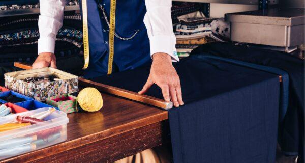 senior-male-fashion-designer-taking-measurement-fabric-wooden-table