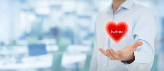 Businessman is in love with his business. Entrepreneur hold virtual heart with text business. Wide banner composition with office in background.