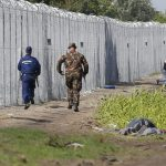 A migrant crosses the boarder fence as soldiers and police try to catch him clo to a migrant collection point in Roszke