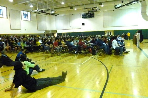 High school students and parents crowd into the gym to discuss college information. Photo by Joyce Liang.