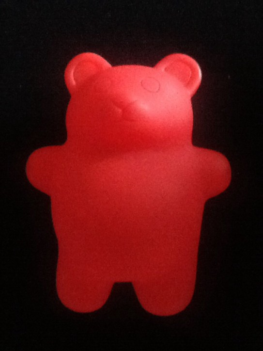 red toy bear presented on a black background