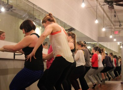 """Hanna makes a quick adjustment on Erin during parallel thigh strengthener at the barre. """"Personalized corrections are the beauty of boutique fitness classes."""""""