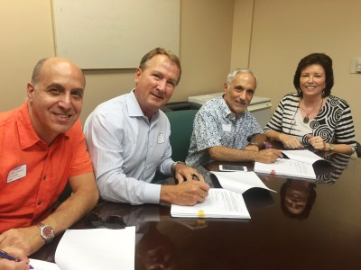 CV Rep's Ron Celona and Gary D. Hall (left) sign the option agreement to purchase the former IMAX theater in Cathedral City with city officials Joe Giarrusso and Tami Scott (right).