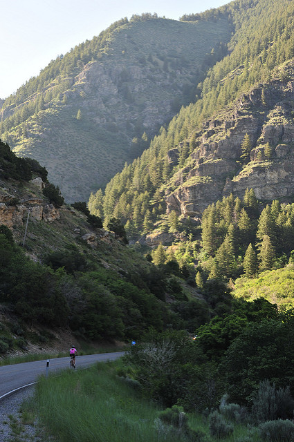 picture of a person riding a bicycle in Blacksmith Fork canyon with towering mountainside to the upper right of the image