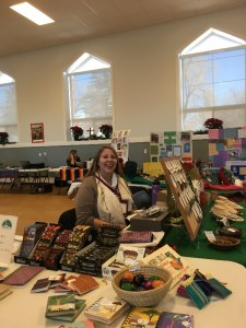 person staffing a table at the Alternative Gift Market for justice