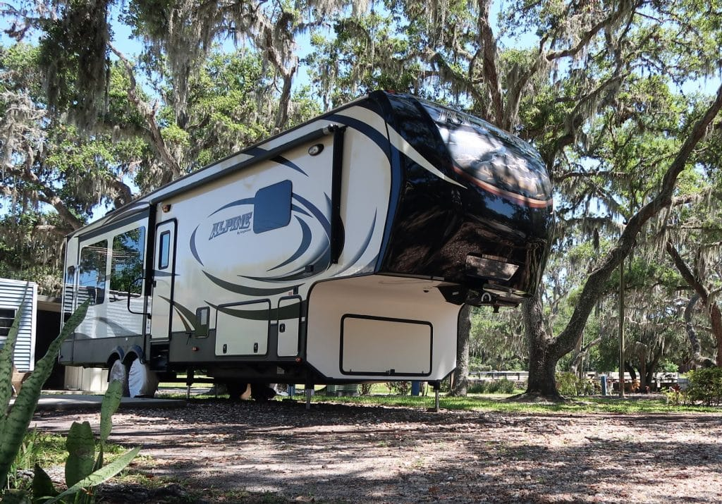 A fifth-wheel parked at a campsite