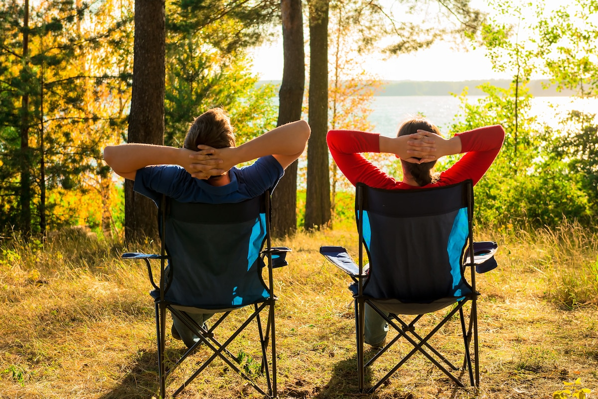 man and woman resting on the lake in camp chairs