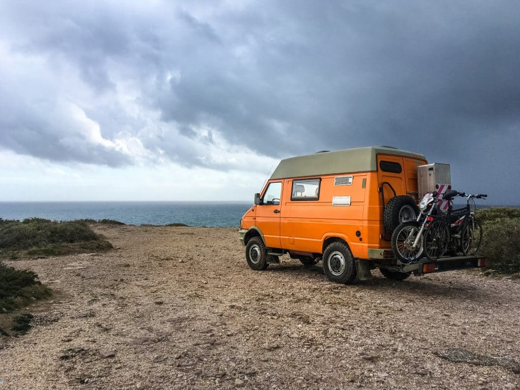 Adventure Vanlife Travel Camping With Motorcycle and Bicycle By 4x4 Car Orange Van In South West Portugal Sagres Algarve Region By Atlantic Ocean Coast Bright Colurful Vibrant Overcast Stormy Sky