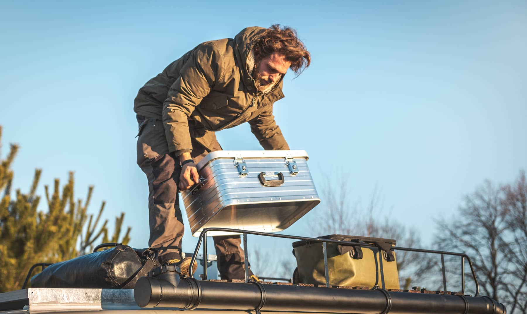 A man is lifting a metal box on the roof of a camper van surrounded by nature