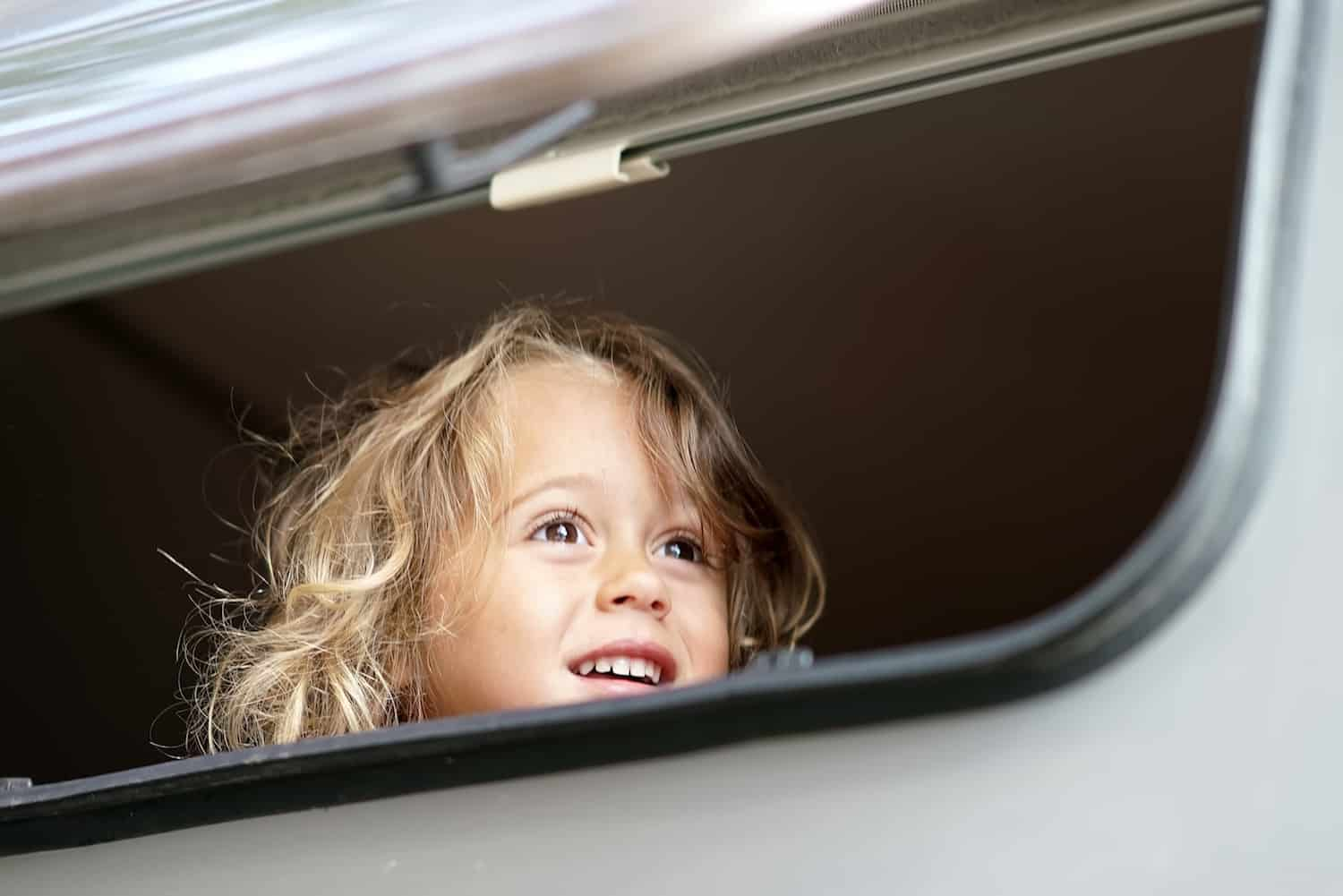 the little girl looks out happy of the camper window