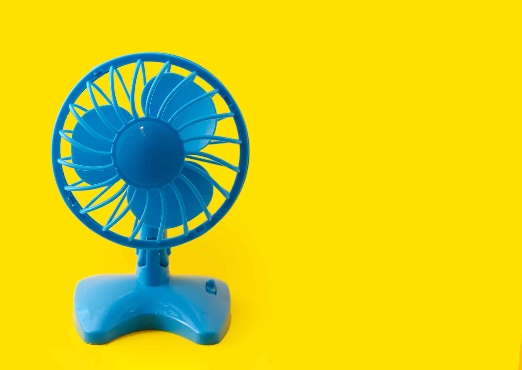 electric blue plastic fan isolated on yellow background
