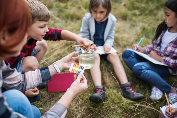 A group of small school children with teacher on field trip in nature, learning science.