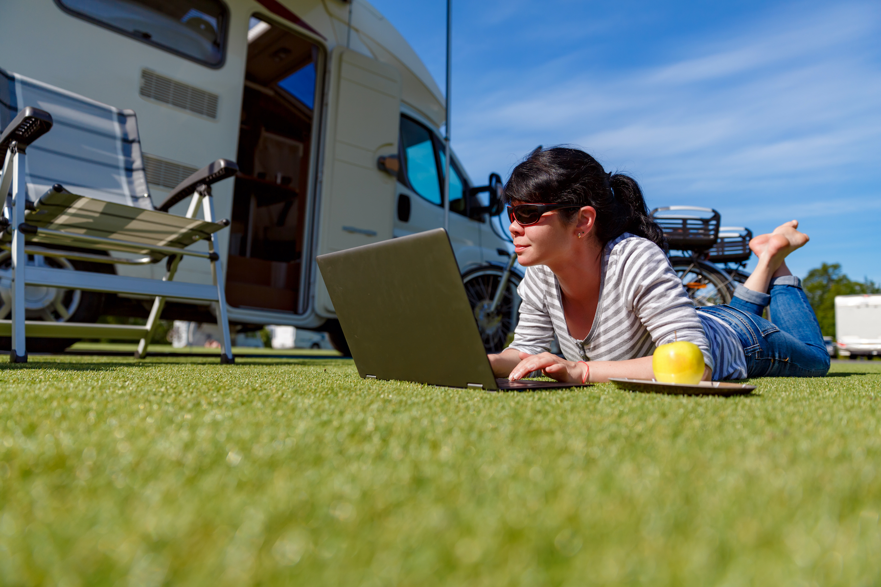 woman on laptop in front of RV.