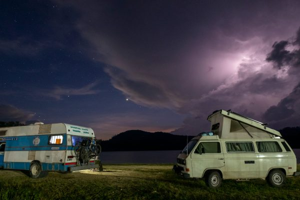 Two camper vans parked at night during a lightning storm