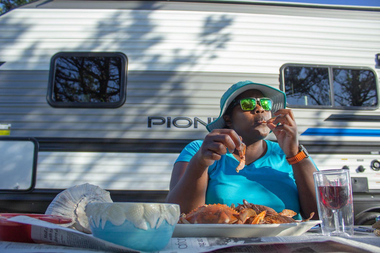 Mirna Valerio eats fresh crab at the campsite.