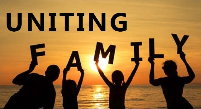 Silhoutte image of a family at the beach at sunset holding up the words family