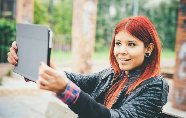 Hispanic female with redhair holds a laptop