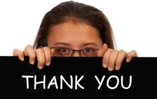 Women holds up a Thank You sign to express gratitude