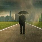 Businessman below storm rain with umbrella , risk and crisis concept .