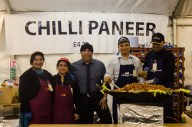 Manager of temple's restaurant with staff serving delicious chilli paneer.