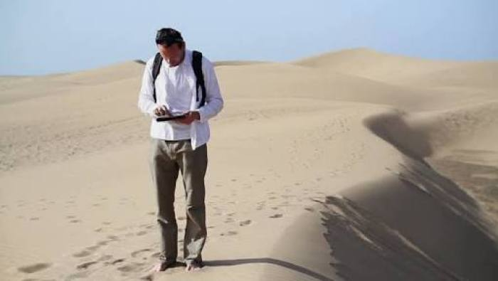 man blogging in a desert on a tablet phone