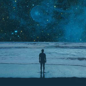 A man stands on a beach, bathed in blue. Space unfolds at his horizon.