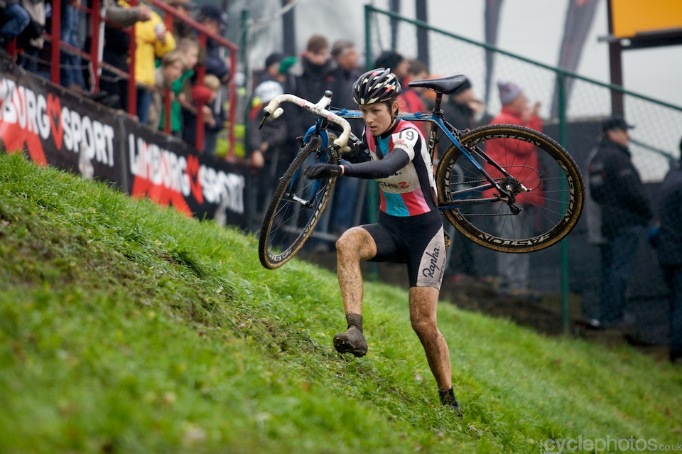 Rapha-Focus rider Julie Krasniak runs up on the muddy hillside.