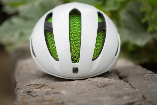 Front view of a white Bontrager XXX WaveCel aero road bike helmet on a stone planter.