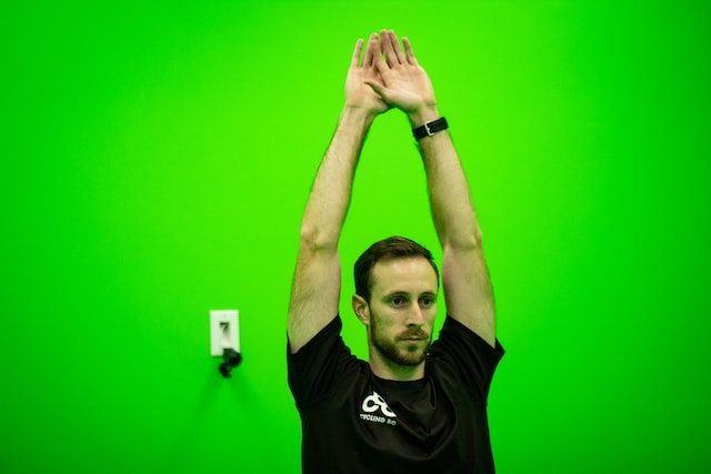 Cycling coach in a motion capture green room reaching above his head.