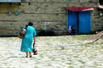 woman fetching water with hers copper vase in Lahic