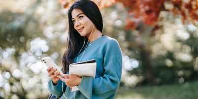 young woman enjoying music using smartphone in garden