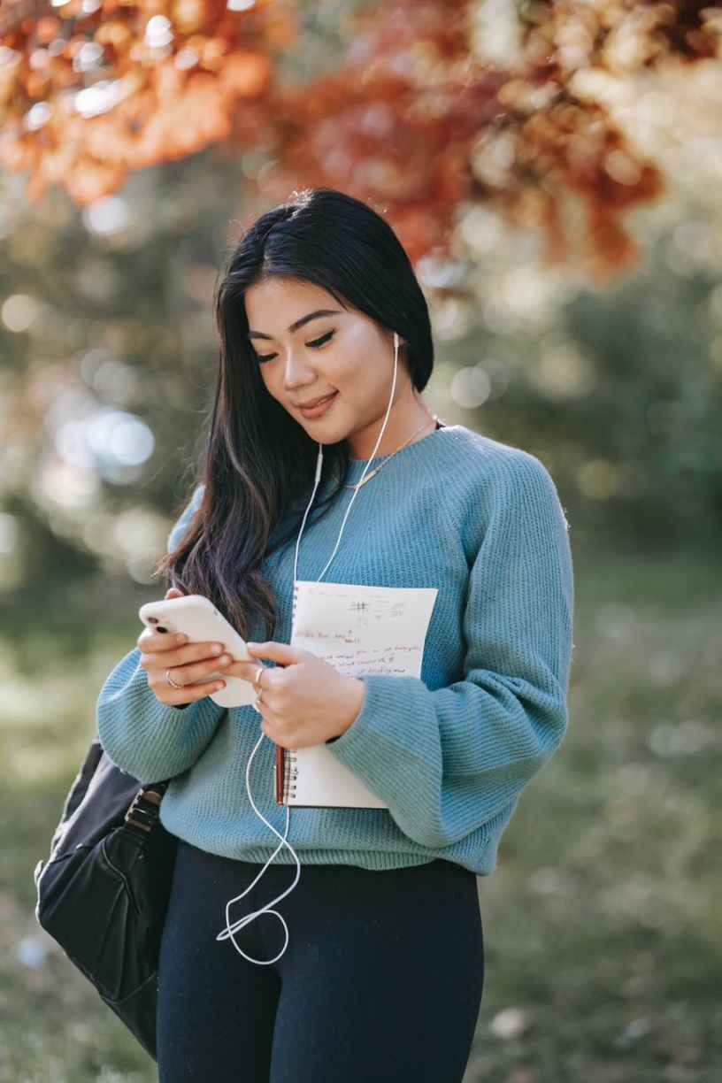 young cheerful woman listening to audio book using smartphone in park