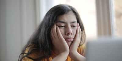 melancholic woman watching video on laptop at home