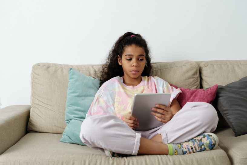 girl in pink shirt sitting on couch
