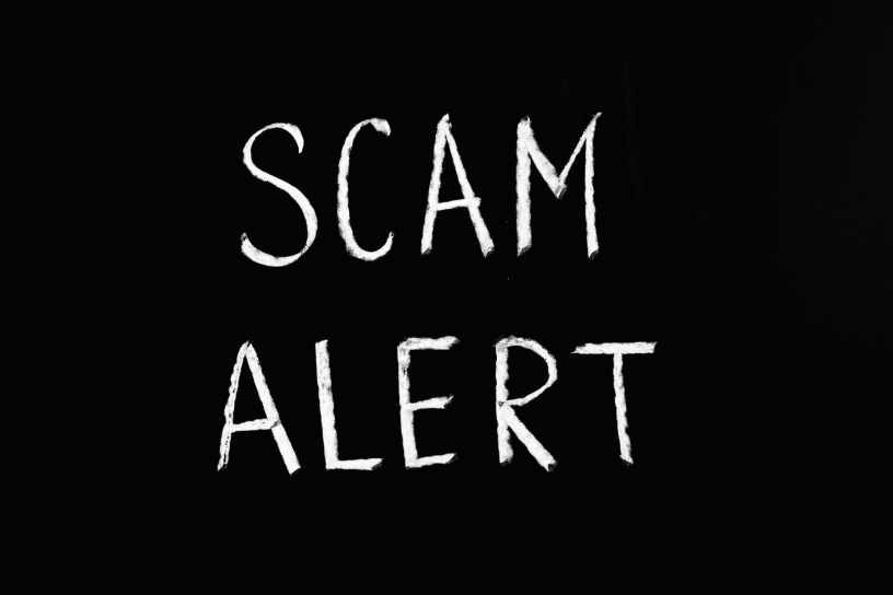 scam alert letting text on black background