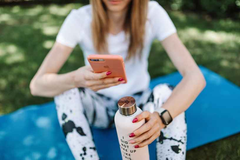 shallow focus photo of a woman holding a water bottle while using her iphone