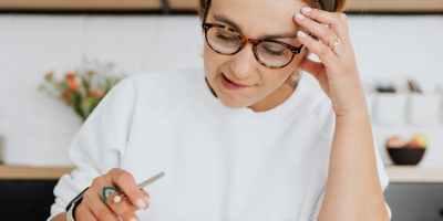 woman in white crew neck t shirt wearing black framed eyeglasses holding white pen