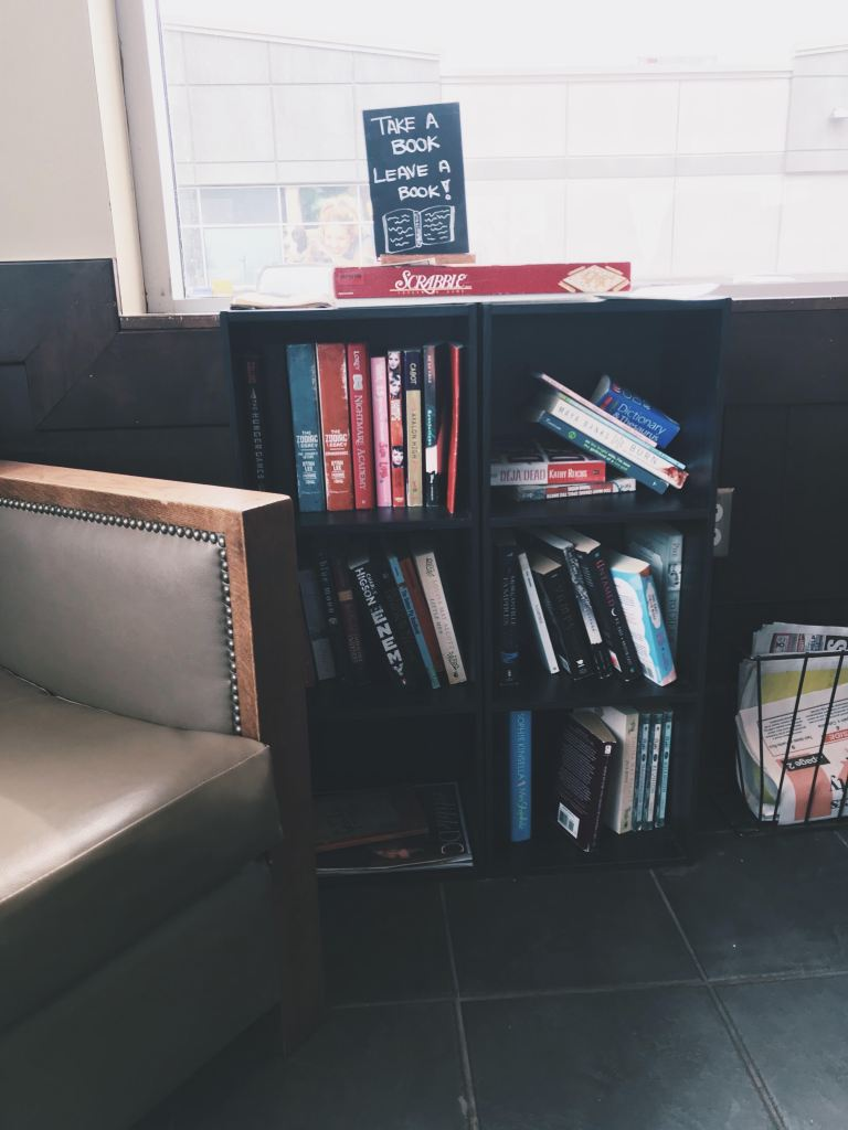 take a book leave a book. bookshelf in a starbucks. ten easy ways you can give back to your community