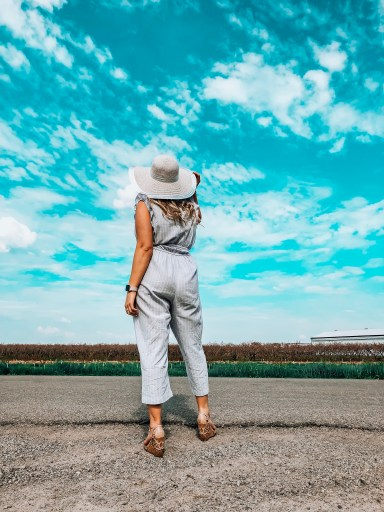 girl standing in wine country, blue skies, tall vines. Blue jumpsuit with white floppy hat and wedge sandals. 5 limiting beliefs that are stopping you from becoming a badass blogger