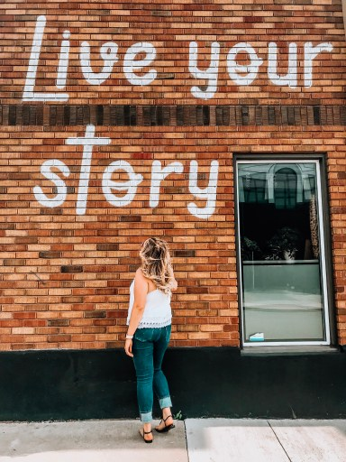 girl in white shirt, blue jeans, black sandals. long curly blonde hair. Brick wall behind that says 'live your story'. monthly favourites may 2019 edition