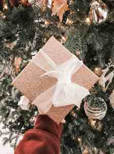 golden glitter present with white bow in front of a golden decorated christmas tree