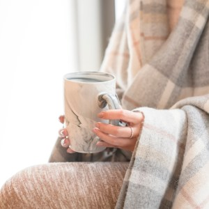 women sitting with blanket, drinking cup of tea. gold ring on her finger.