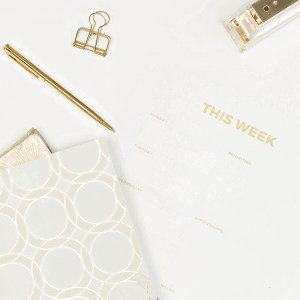 flat lay of planning sheets, gold pens, stapler, binder clips and folders. Gold and white palette