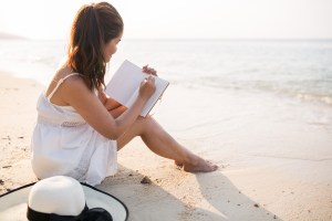 girl sitting on beach in white dress with sunhat, writing in book.