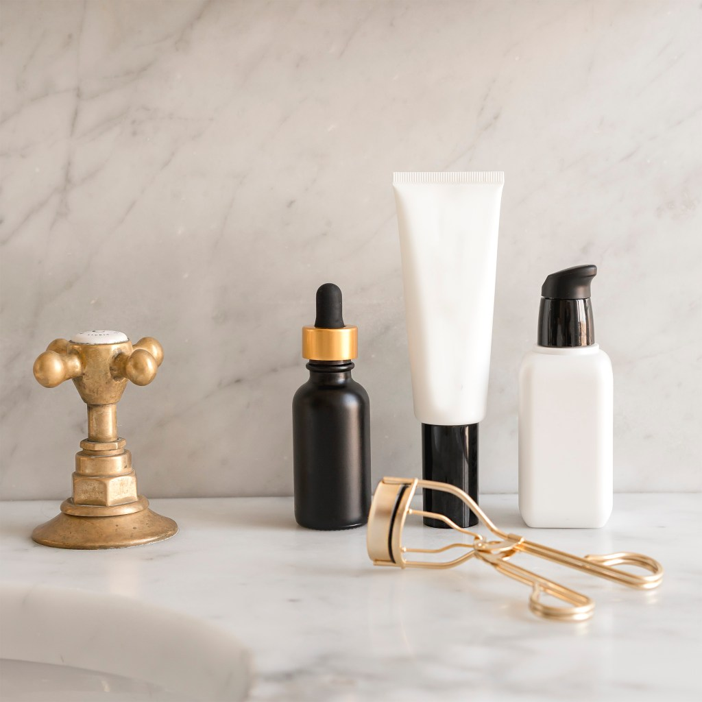 beauty products sitting on bathroom counter. eyelash curler. 5 secrets to shopping high end beauty on a budget.