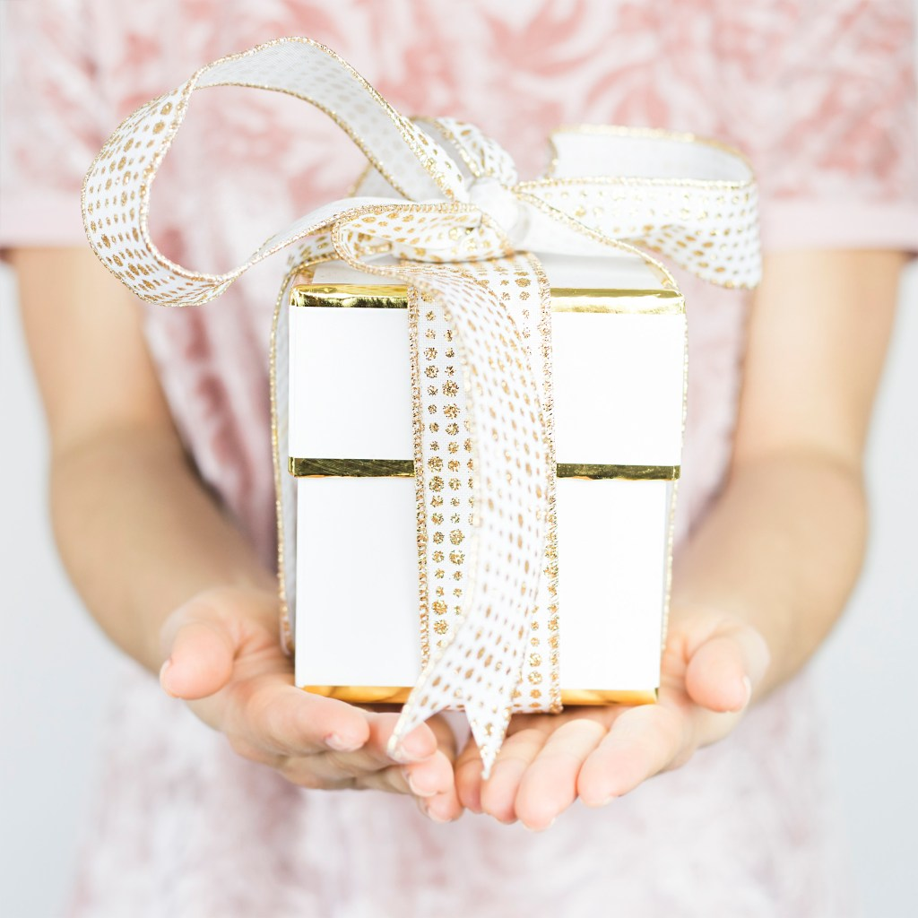 girl in pink shirt holding white and gold gift with a big bow. The ultimate gift guide for her.