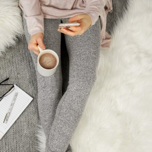 woman sitting in grey leggings, on phone with cup of coffee in hand. 10 signs you're stuck in a rut -and how to get out